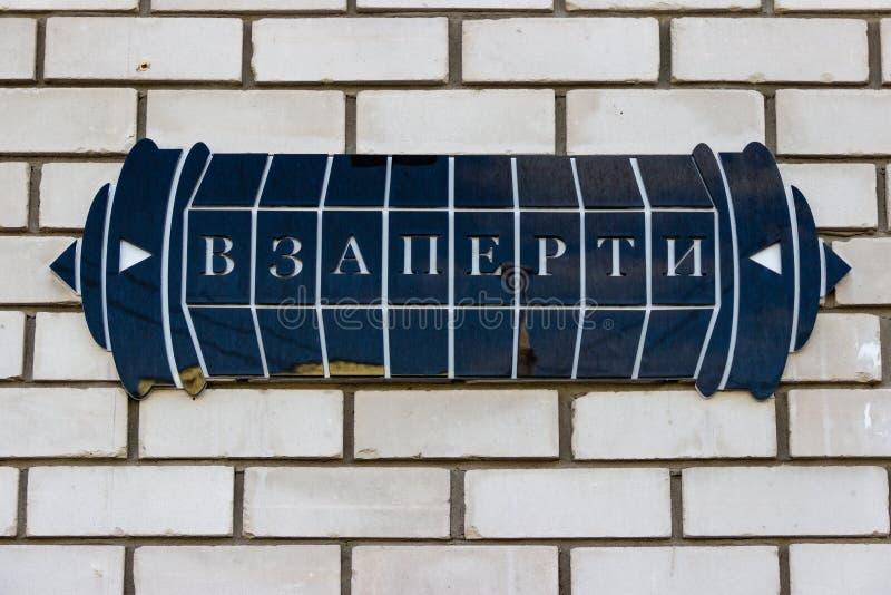 与在一个白色砖墙上锁的题字的一个标志 免版税库存图片