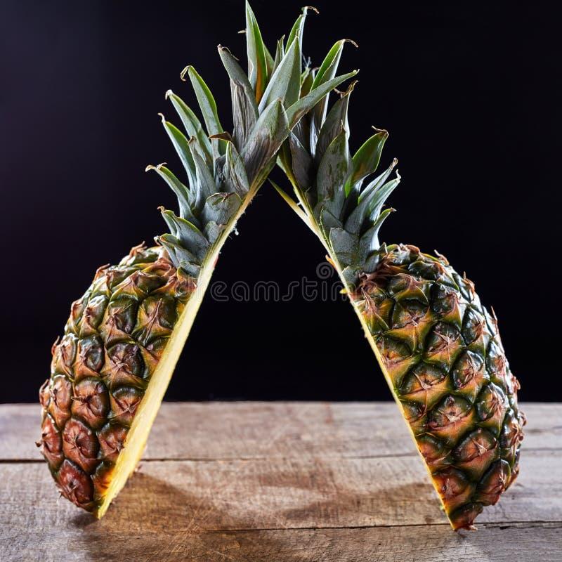 与在一张木桌上提出的绿色叶子的热带成熟果子菠萝在与拷贝空间的黑暗的背景附近 免版税库存照片