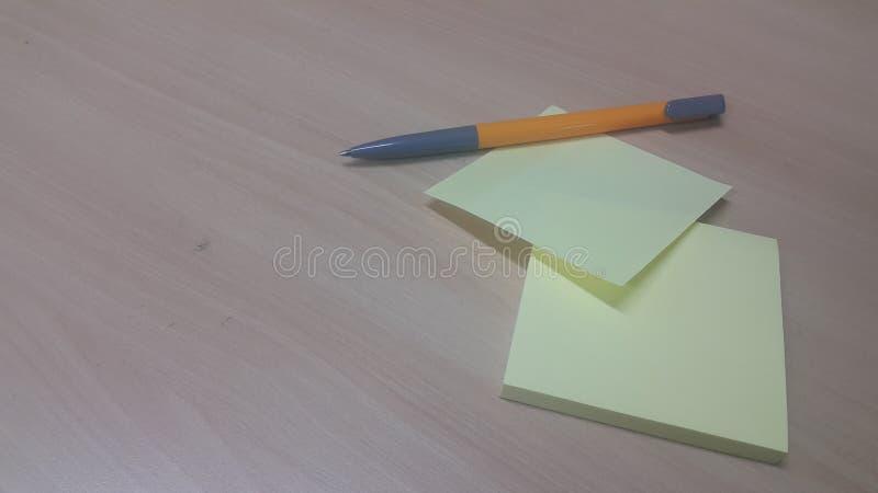 与在一张木桌安置的笔的黄色稠粘的便条纸 库存照片