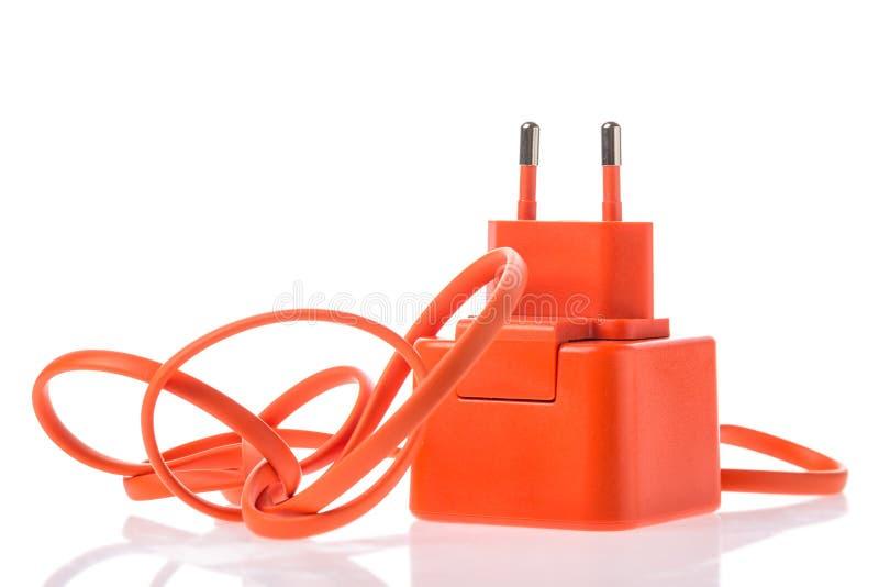 与在与反射的白色背景隔绝的usb缆绳的橙色适配器充电器 电话或其他电子设备充电器 库存图片