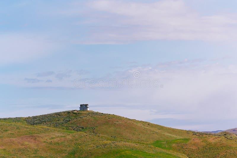 与在与多云惊人的天空的上面建造的一个木房子的美丽的青山 免版税图库摄影