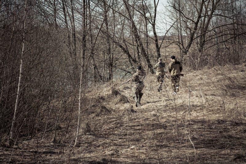 与在伪装窃取在有干燥叶子的春天森林里的猎人的狩猎场面在狩猎期期间 免版税库存照片