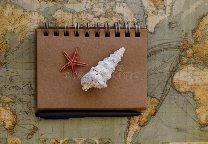 与在地图和贝壳的旅行平的位置安置的笔记薄 库存照片