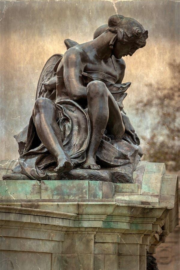 与在女王Victo附近的四个古铜色雕象之一的老照片 免版税库存照片