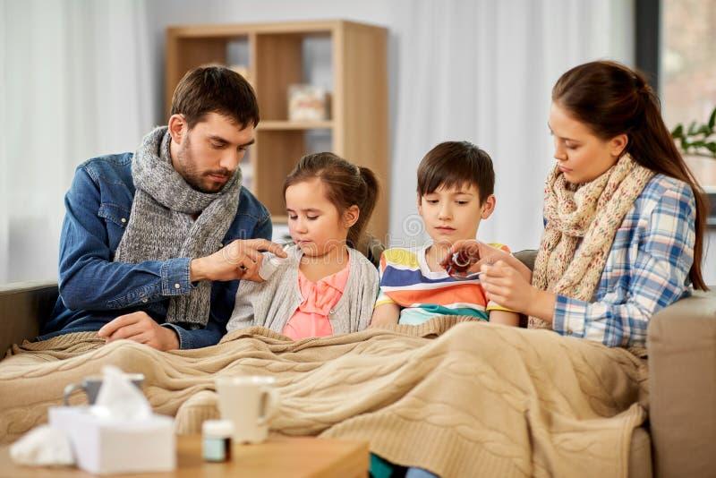 与在家对待不适的孩子的医学的家庭 免版税库存照片