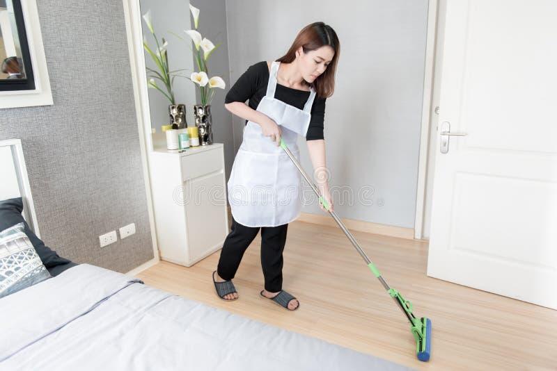 与在家拖把的年轻佣人清洁地板,清洁服务概念 免版税库存照片