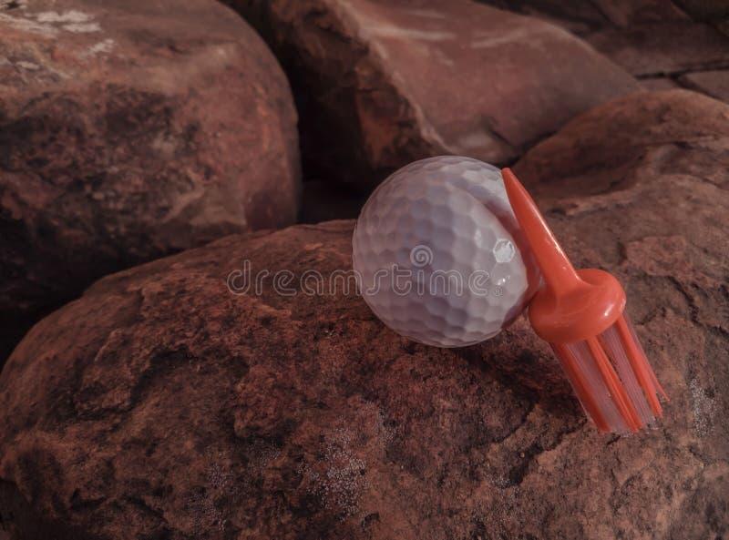 与在岩石表面安置的橙色刷子发球区域的白色球 免版税库存照片