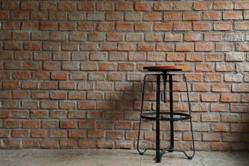 与在工业和简单派设计的土气砖和混凝土墙样式投下的阴影的简单的椅子 图库摄影