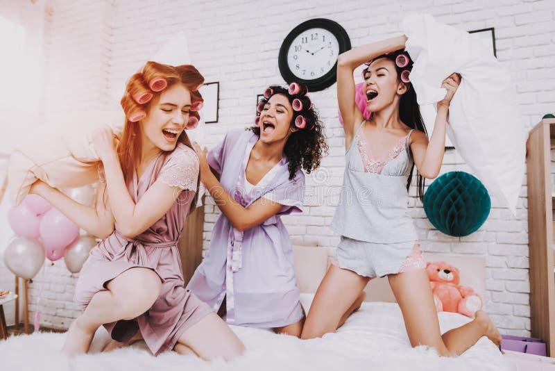 与在床上的三个愉快的女孩白色枕头战斗 免版税库存图片