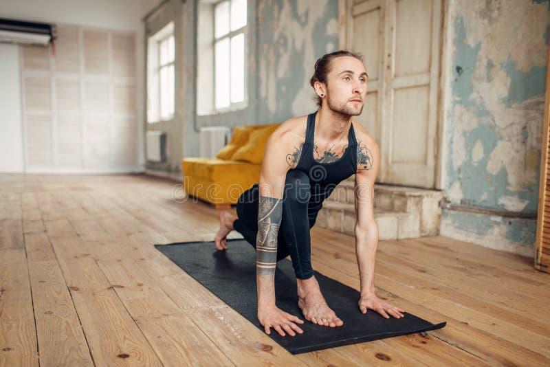与在手边做锻炼的纹身花刺的男性瑜伽