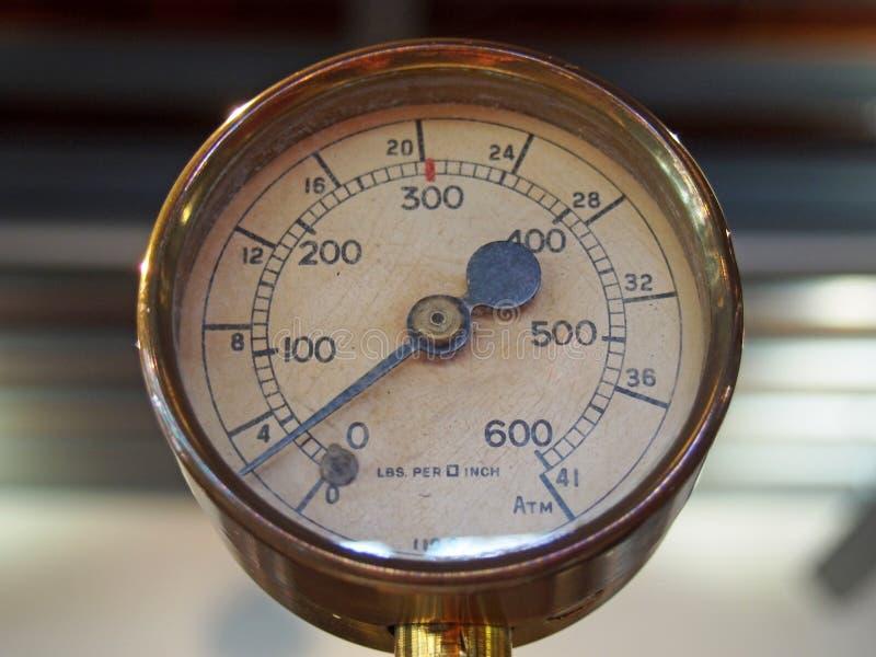 与在数字和一根黑金属针标记的一个圆的拨号盘的老发光的黄铜圆的压力表 图库摄影