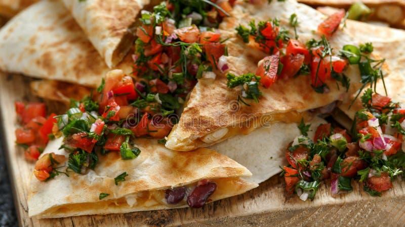 与在有自创新鲜的辣调味汁的土气木砧板和乳酪的墨西哥美食油炸玉米粉饼供食的鸡 免版税库存图片