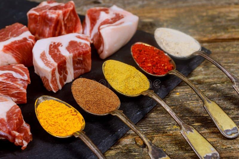 与在木桌上的新未加工的牛肉entrecote与香料成份 免版税库存图片