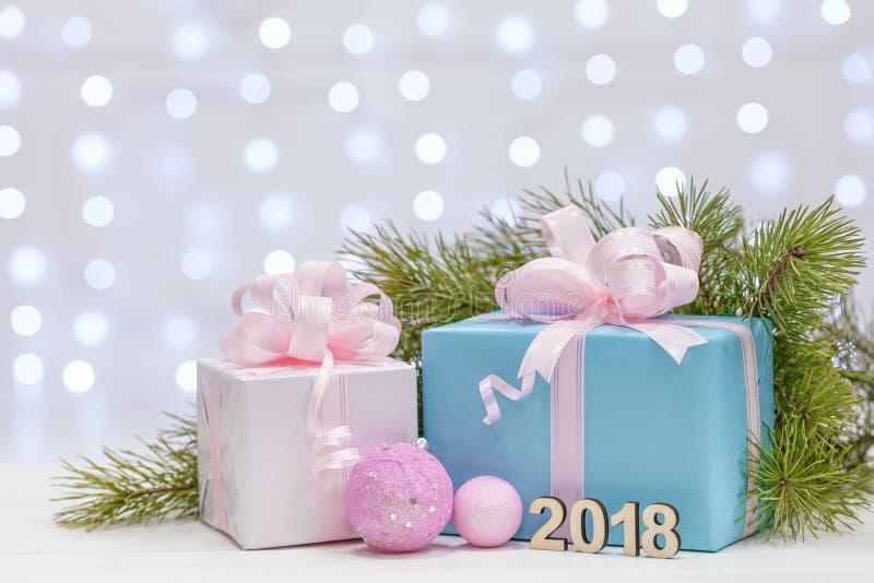 与在桃红色和赤裸纸包裹的大弓的圣诞节礼物,木表面上的谎言与云杉的分支 免版税库存图片