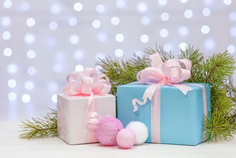 与在桃红色和赤裸纸包裹的大弓的圣诞节礼物,木表面上的谎言与云杉的分支 库存图片