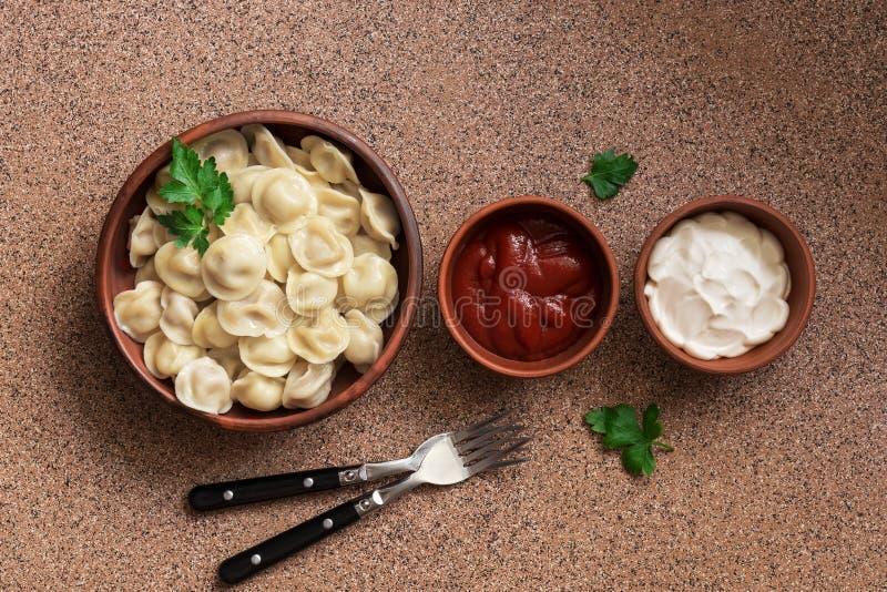与在棕色石背景连续安排的酸性稀奶油和番茄酱的俄国食物pelmeni肉饺子 顶上的看法,拷贝 免版税库存照片