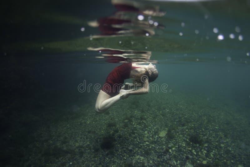 与在水面下一只红色野兽的俏丽的信奉瑜伽者跳舞 库存图片