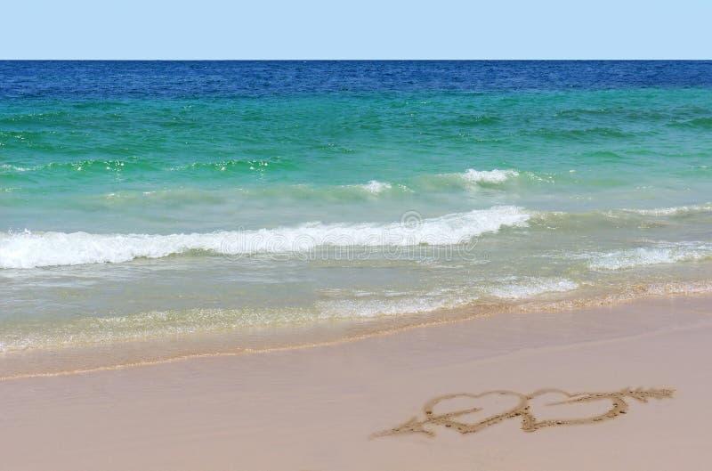 与在海滩的沙子画的箭头的两心脏 概念亲吻妇女的爱人 免版税库存照片