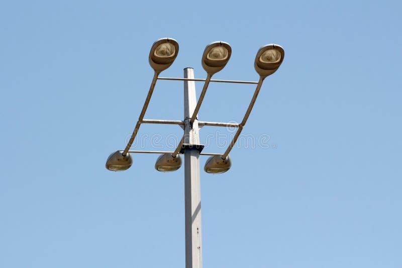 与在清楚的天空蔚蓝的上面登上的六台大现代轻的反射器的高强的金属电线杆  免版税图库摄影