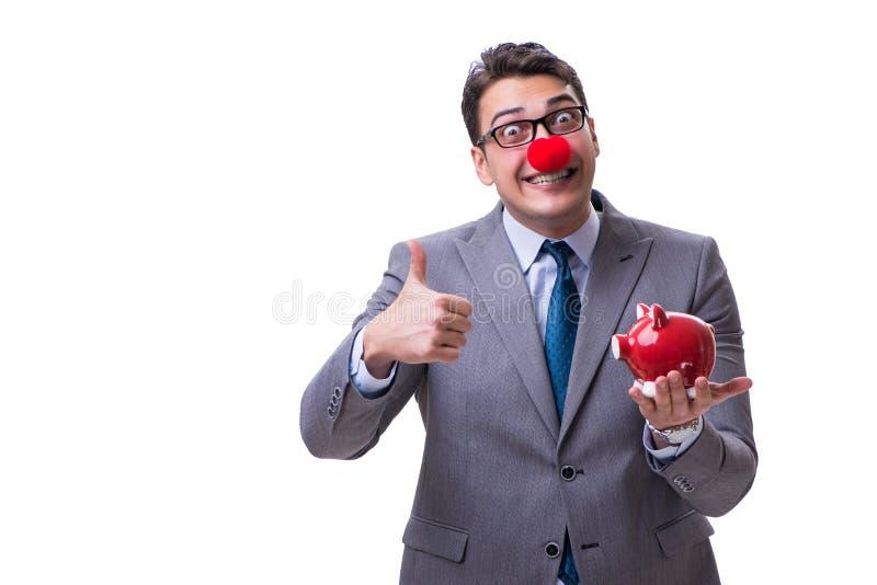 与在白色后面隔绝的存钱罐的滑稽的小丑商人 免版税库存图片