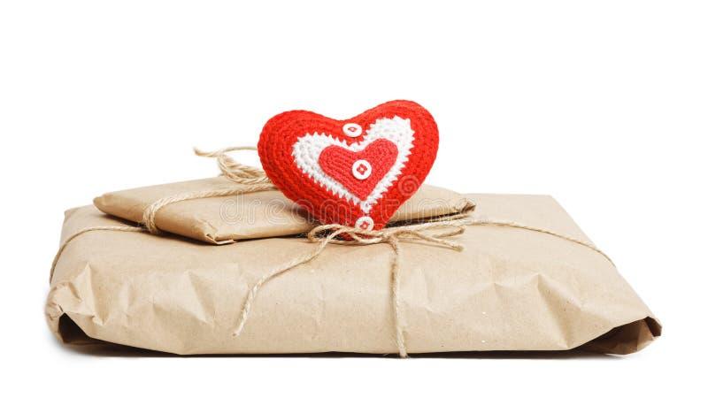 与在白色和红色心脏的小包隔绝的牛皮纸 图库摄影