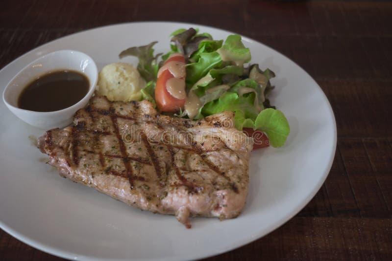 与在白色板材服务的烤菜的牛排 库存照片