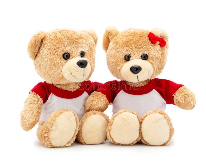 与在白色背景和红色弓的夫妇可爱的棕色玩具熊隔绝的T恤杉 图库摄影