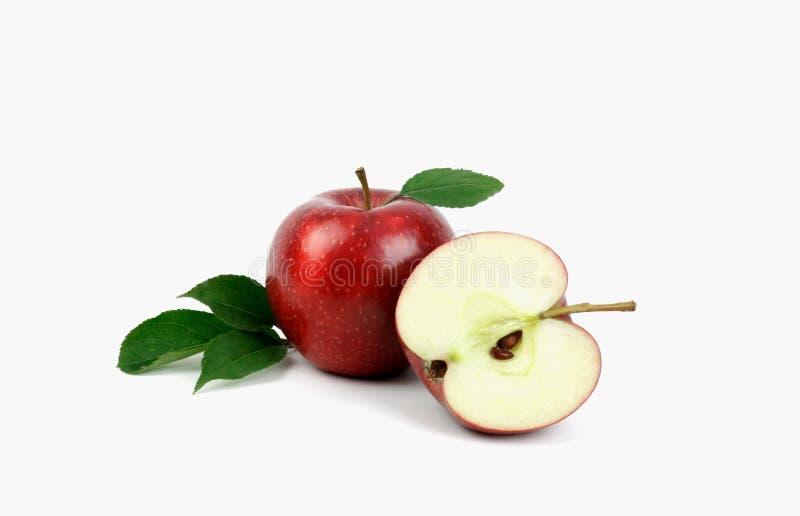 与在白色背景和绿色苹果叶子的成熟红色苹果果子隔绝的苹果一半 免版税库存照片