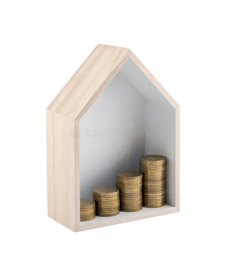 与在白色背景隔绝的上升的金黄硬币的木房子形状 免版税库存图片