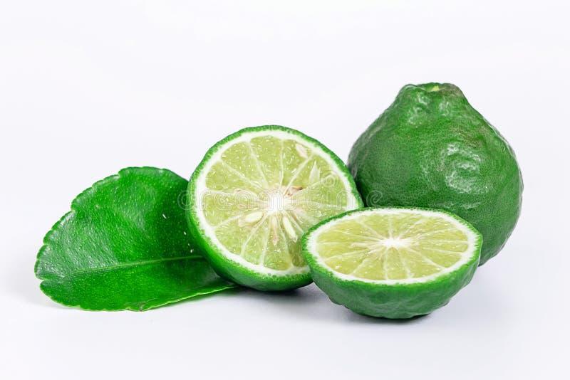 与在白色背景隔绝的切成两半的和绿色叶子的新鲜的香柠檬果子 免版税库存图片
