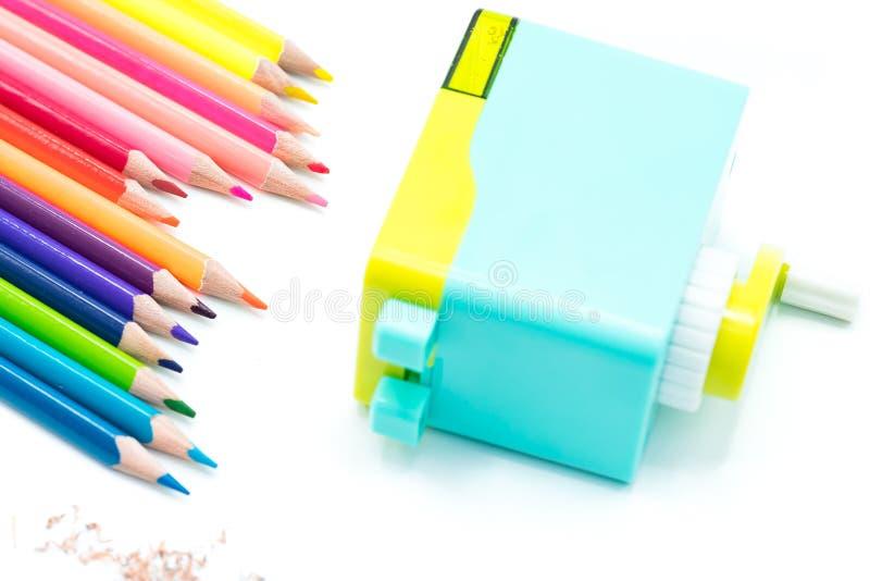 与在白色背景隔绝的木五颜六色的铅笔的淡色蓝色黄色转台式铅笔刀削片,回到学校 库存图片