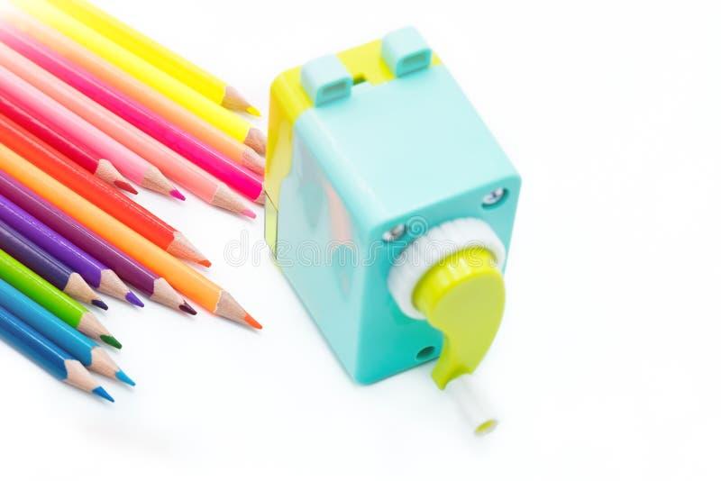 与在白色背景隔绝的木五颜六色的铅笔的淡色蓝色黄色转台式铅笔刀削片,回到学校 免版税库存图片