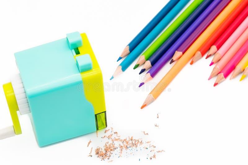 与在白色背景隔绝的木五颜六色的铅笔的淡色蓝色黄色转台式铅笔刀削片,回到学校 免版税库存照片