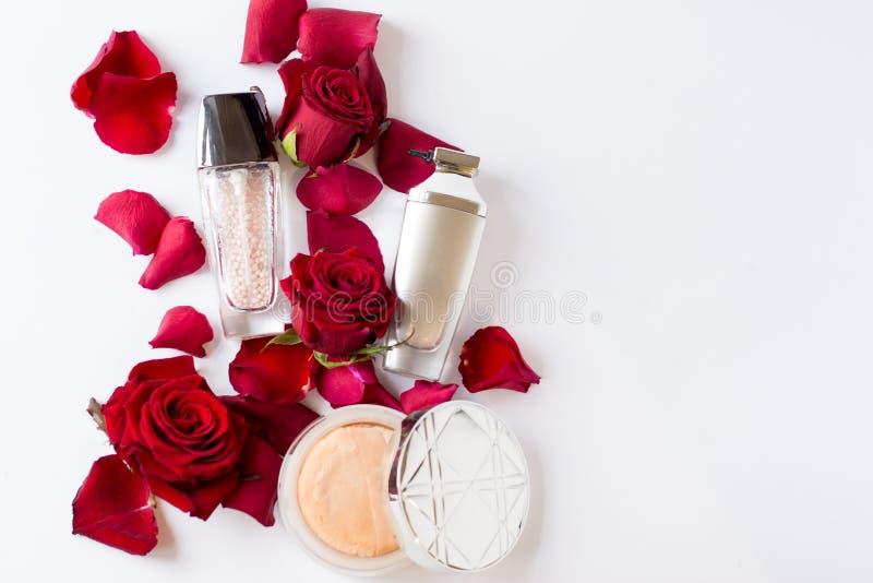 与在白色背景隔绝的红色花的构成化妆用品 r 图库摄影