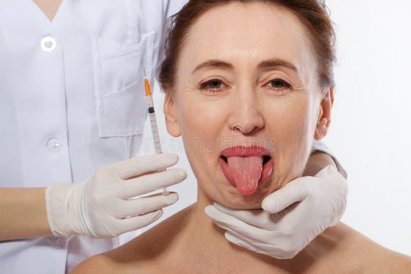与在白色背景隔绝的舌头的妇女面孔 装饰性的处理 成熟在整容手术白人妇女 面孔射入和胶原,滑稽 免版税库存照片