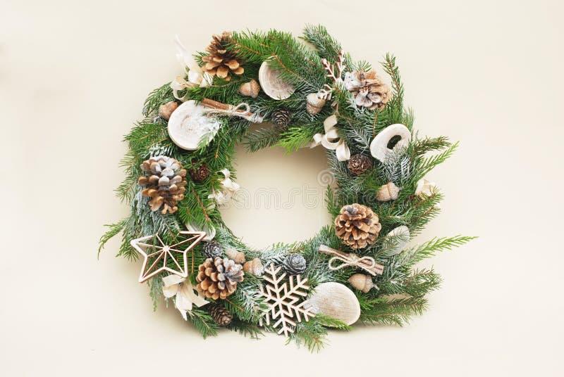 与在白色背景隔绝的装饰的绿色圣诞节花圈 与自然辅助部件的Eco样式:pinecones 免版税库存照片