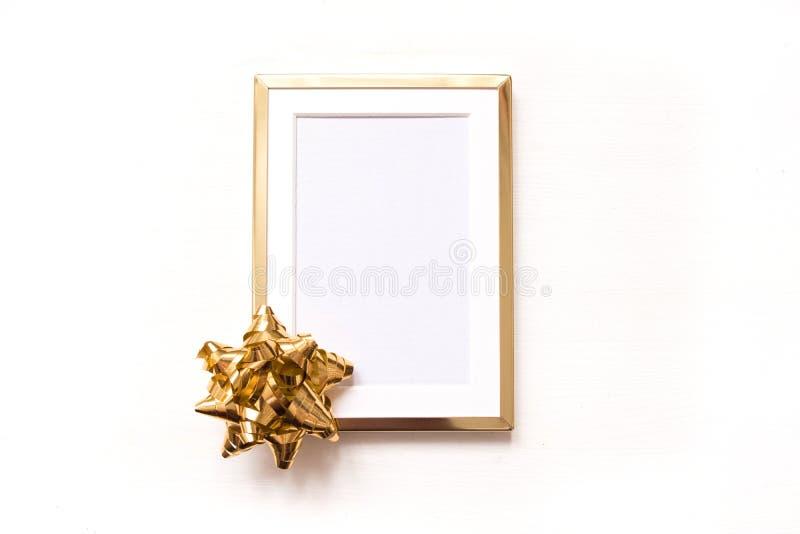 与在白色背景隔绝的金弓的金黄框架 平冬天minimalistic的圣诞节放置 免版税库存照片