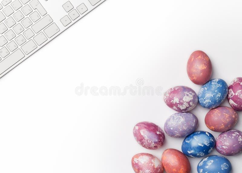 与在白色背景隔绝的键盘的复活节彩蛋 库存图片