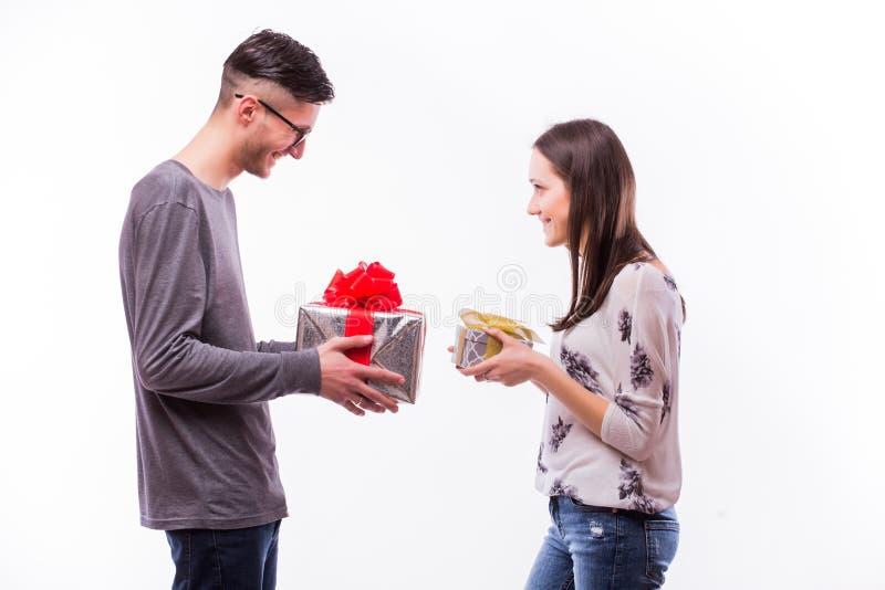 与在白色背景隔绝的礼物的愉快的年轻行家夫妇变动 免版税库存照片