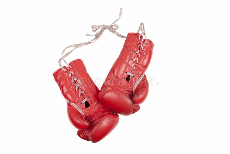 与在白色背景隔绝的鞋带的老使用的和被打击的红色皮革拳击手套 免版税库存照片