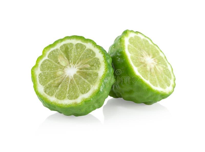 与在白色背景,草本和医疗隔绝的绿色叶子的新香柠檬果子切片 图库摄影