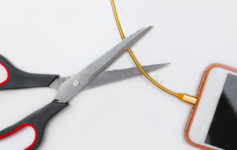 与在白色隔绝的剪刀的切口智能手机充电的缆绳 库存照片