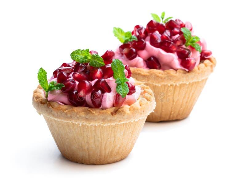 与在白色隔绝的桃红色奶油和石榴种子的微型馅饼 库存照片
