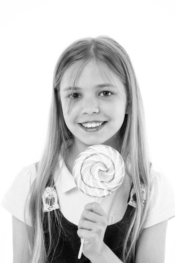 与在白色隔绝的棒棒糖的女孩微笑 微笑用在棍子的糖果的小孩子 愉快的孩子用漩涡焦糖 食物 库存图片