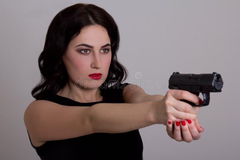 与在白色隔绝的枪的严肃的性感的女孩射击 库存图片