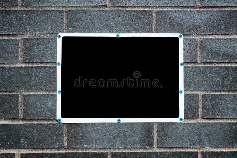 与在砖墙登上的白色框架的空白的黑标志 免版税图库摄影