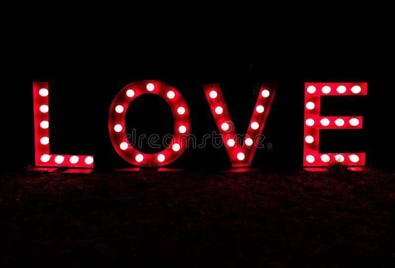 与在红色的明亮地被点燃的信件中写道的词和文本爱的黑夜 库存图片