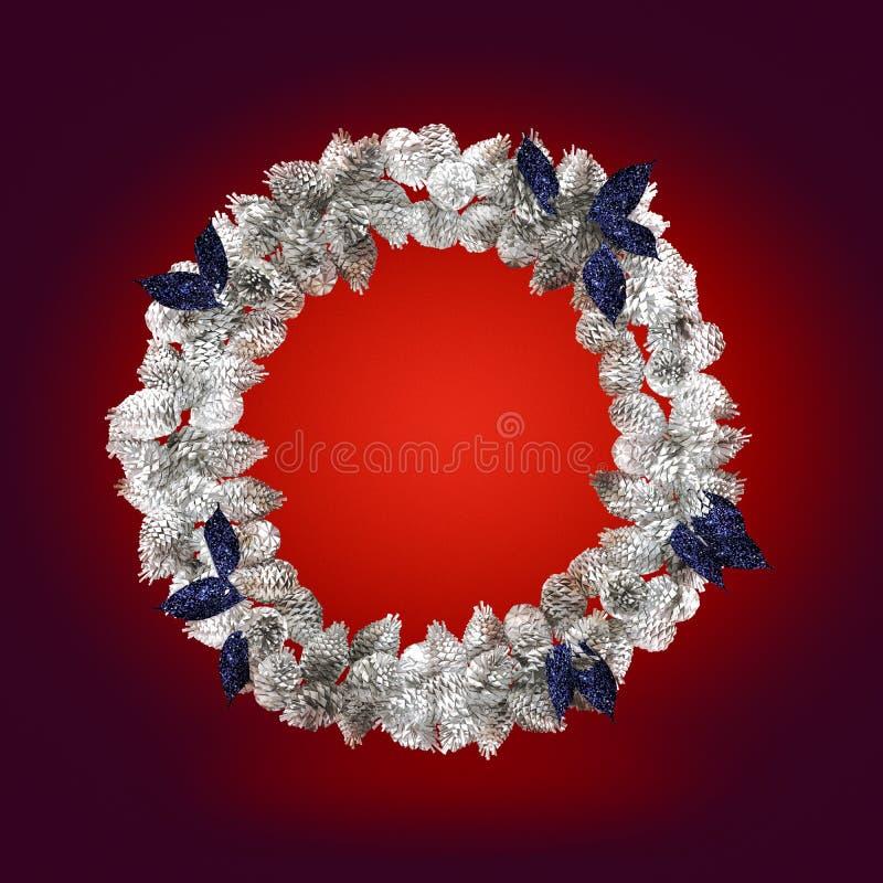 与在红色背景隔绝的装饰的银色圣诞节花圈 免版税库存照片