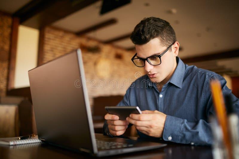 与在膝上型计算机观看的录影的工作分散的英俊的商人在智能手机 拿着手机的自由职业者 免版税库存图片