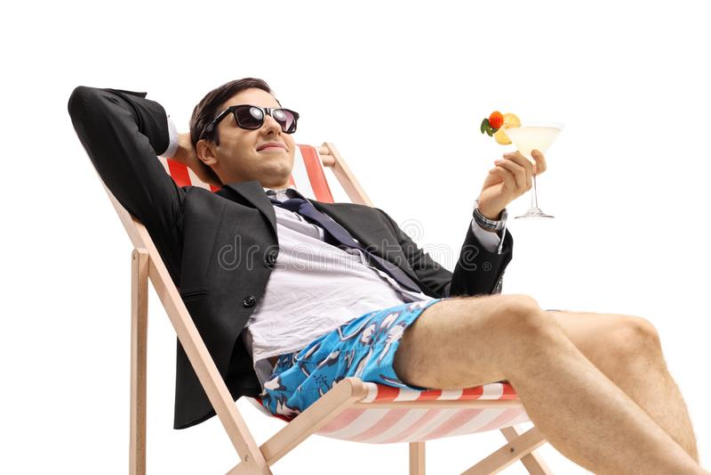 与在轻便折叠躺椅的鸡尾酒的商人 免版税库存图片